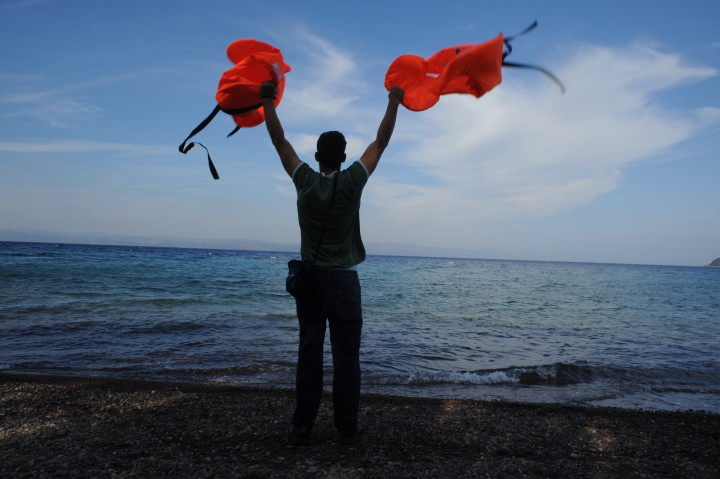 October 5, 2015-Lesvos, North-east Aegean sea, Greece: Man moves his hands holding two life-jackets, in order to attrack the refugees' boats. Refugees arrive to the coast of the Greek island Lesvos, into small plastic and cheap boats from the Turkish land. (Maro Kouri)