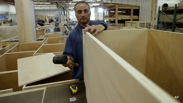 In a photo from Friday, July 8, 2016, inmate William Garrett works on a cabinet at the Habitat for Humanity Prison Build at the Ionia Correctional Facility in Ionia, Mich. Few states have been more aggressive in releasing inmates and diverting offenders than Michigan, where the prison system has long threatened the state's capacity to fund universities and other basics of government. But the $2 billion annual cost remains steep, exacerbated by a boomerang found here and across the country: the large number of inmates who wind up back behind bars again. Now Michigan leaders, frustrated that their downsizing efforts have hit a wall, are trying novel, more hands-on methods to ensure that prisoners leave with a job in hand. (AP Photo/Carlos Osorio)
