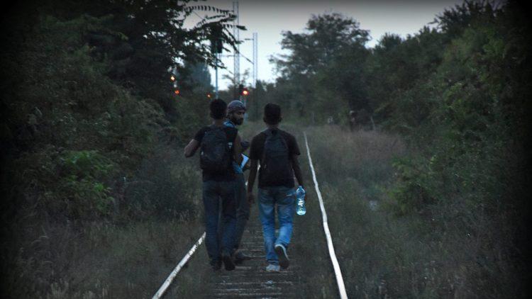 Refugiados caminado por las vias